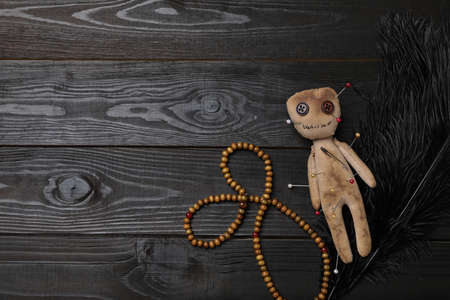 Voodoo doll pierced with pins, beads and feather on black wooden table, flat lay. Space for text
