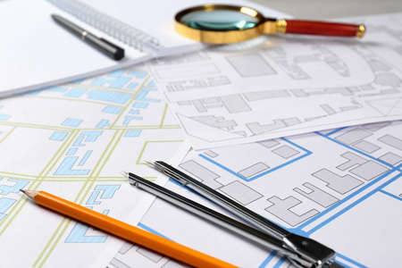 Office stationery and cadastral maps of territory with buildings on table