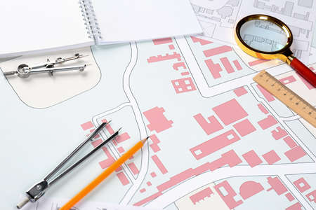 Office stationery on cadastral maps of territory with buildings