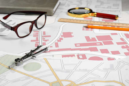 Office stationery and eyeglasses on cadastral maps of territory with buildings Reklamní fotografie