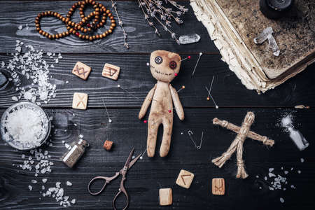 Voodoo doll with pins surrounded by ceremonial items on black wooden table, flat lay Zdjęcie Seryjne