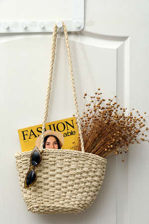 Stylish beach bag with beautiful dried flowers, sunglasses and magazine hanging on white wooden door Standard-Bild