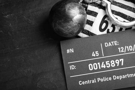 Metal ball with chain, prison uniform and mugshot letter board on black table, flat lay. Space for text