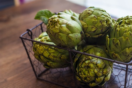 Fresh organic artichokes over a dark blue napkin with knife and lemon and with metal basket with artichokes over a rustic wooden background. Top View
