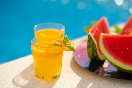 Summer holiday tropical concept. Fresh orange juice and watermelon juice and pineapple on border of a swimming pool.