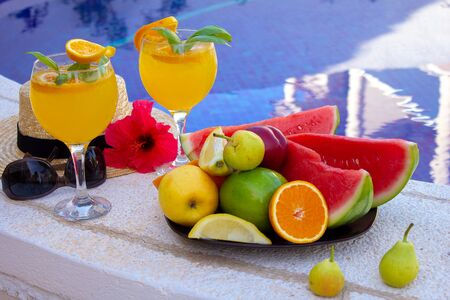 Watermelon fresh juice smoothie drink glass with flower, sunglasses, slippers and straw hat on border of a swimming pool - holiday tropical concept Archivio Fotografico - 134866959