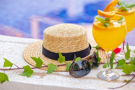 Watermelon fresh juice smoothie drink glass with flower, sunglasses, slippers and straw hat on border of a swimming pool - holiday tropical concept Archivio Fotografico - 134866963
