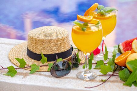 Watermelon fresh juice smoothie drink glass with flower, sunglasses, slippers and straw hat on border of a swimming pool - holiday tropical concept Archivio Fotografico - 134866964