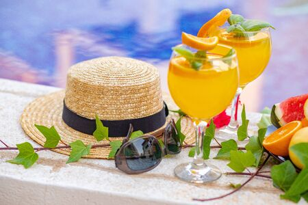Watermelon fresh juice smoothie drink glass with flower, sunglasses, slippers and straw hat on border of a swimming pool - holiday tropical concept Archivio Fotografico - 134866973