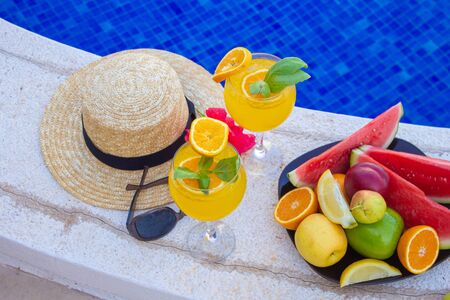 Watermelon fresh juice smoothie drink glass with flower, sunglasses, slippers and straw hat on border of a swimming pool - holiday tropical concept Archivio Fotografico - 134866974
