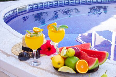 Watermelon fresh juice smoothie drink glass with flower, sunglasses, slippers and straw hat on border of a swimming pool - holiday tropical concept Archivio Fotografico - 134866976