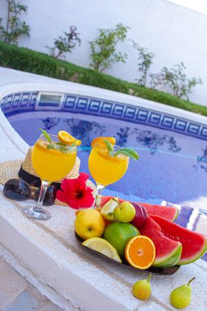 Watermelon fresh juice smoothie drink glass with flower, sunglasses, slippers and straw hat on border of a swimming pool - holiday tropical concept Archivio Fotografico - 134866981