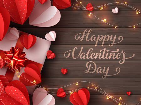 Happy Valentines day greeting card. Decorative paper cut hearts, gift box, garland with handwritten lettering text on brown wooden background. Vector illustration. 向量圖像