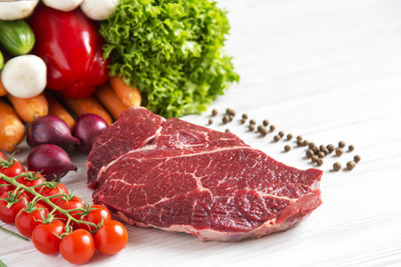 Raw meat, different vegetables and fruits on a wooden background. Healthy food.