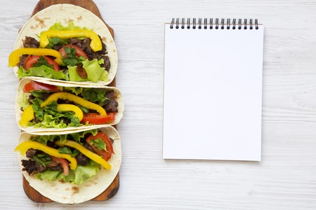Tacos with pork and vegetables with notebook. Mexican kitchen. White wooden background. Top view, flat, overhead. Copy space and text area.