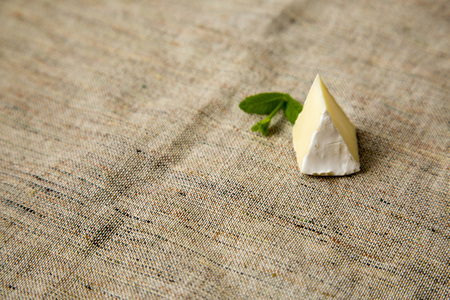 A piece of brie or camembert cheese on rustic background. Milk production. Side view. Copy space.