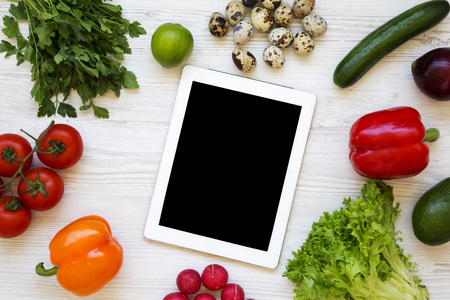 Healthy food concept. Raw fruits and vegetables wirh tablet on a white wooden background. Flat lay. Top view. From above.