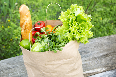 A full paper bag of healthy products stands on the wooden table. Closeup.