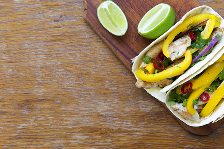 Tacos with grilled chicken fillet, fresh vegetables, lime on wooden board. Top view, from above. Copy space.