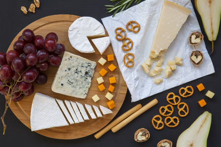 Tasting cheese with fruits, pretzels and walnuts on dark background. Food for wine, top view.