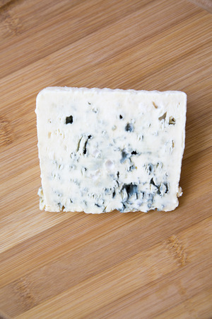 Blue cheese on wooden board. Top view. From above