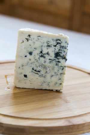 Blue cheese on wooden board. Side view. Closeup Standard-Bild