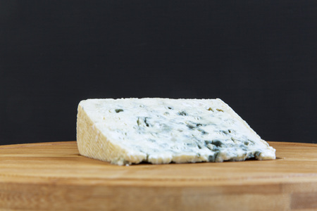 Blue cheese on wooden board. Closeup.