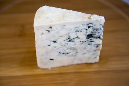 Blue cheese on wooden board. Side view. Standard-Bild