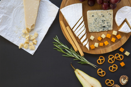Tasting different types of cheeses with fruits, pretzels walnuts and bread sticks on dark background. Food for wine, romantic. Top view.