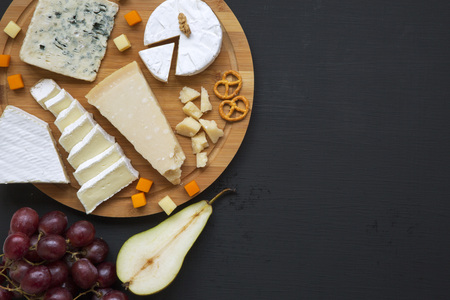 Tasting cheese with fruits, pretzels walnuts and bread sticks on dark background, from above. Food for wine. Top view. Copy space. Standard-Bild