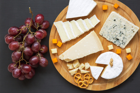 Tasting cheese with grapes, pretzels and walnuts on dark background, from above. Food for wine. Top view.