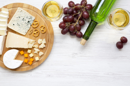 Tasting cheese with wine, grapes, walnuts and pretzels on wooden background. Food for romantic. From above. Top view. Flat lay.