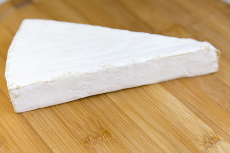 Brie cheese on wooden board. Side view.