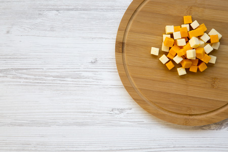 Pieces of mimolette and edam cheeses on wooden board. Top view. Copy space.