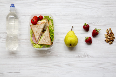 Healthy school lunch box with fresh organic vegetables sandwich, walnuts, fruits and bottle of water on white wooden background, flat lay. From above. Copy space.