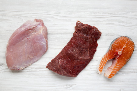 Uncooked raw salmon steak, beef meat and turkey breast on white wooden background, top view. Flat lay. From above. Standard-Bild