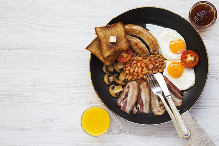 Full English breakfast in a pan with fried eggs, bacon, sausages, beans, toasts and orange juice on white wooden background, top view. Flat lay. From above. Space for text. Stockfoto