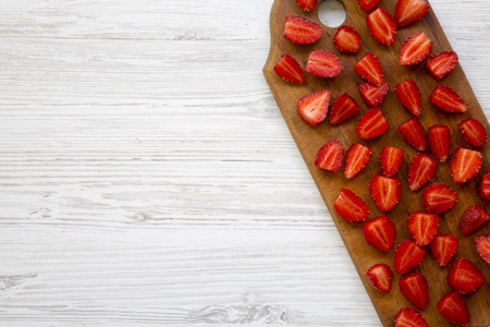 Fresh ripe strawberries on wooden cutting board, top view. Copy space. White wooden table. From above, flat lay.
