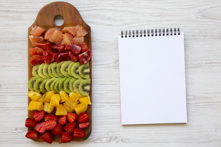 Top view, chopped fresh fruits arranged on cutting board and notebook on white wooden background. Flat lay.