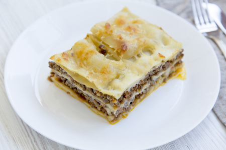 Delicious beef lasagne served on a white round plate, white wooden background. Side view. Stock fotó