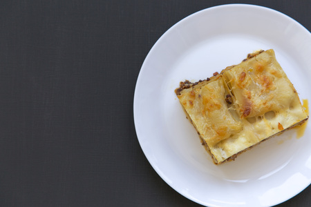 Traditional beef lasagne on a white round plate, dark background, top view. Flat lay, from above. Copy space. Stock fotó