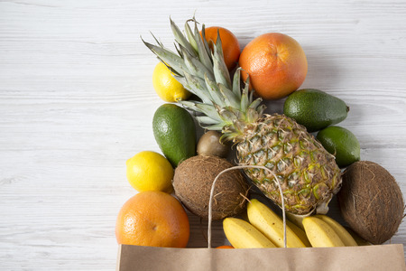 Paper bag of various exotic fruits on white wooden background, top view. Copy space. Flat-lay. Reklamní fotografie
