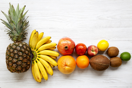 Fresh tropical fruit on a white wooden background, from above. Copy space. Flat lay.