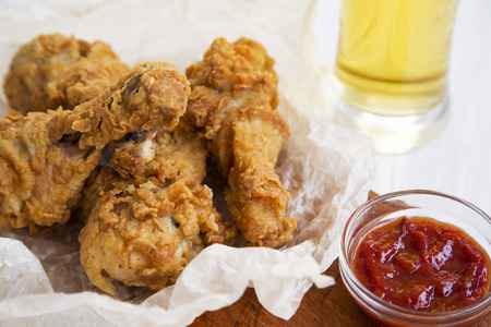 Fried chicken legs with sauce and cold beer, close-up.