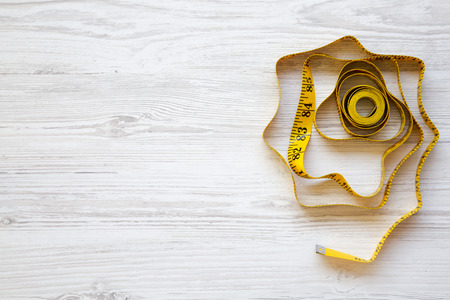Yellow measuring tape on white wooden table, top view. Copy space.