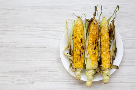 Grilled corn cobs on a round plate over white wooden surface, top view. From above, overhead, flat lay. Copy space and text area. 스톡 콘텐츠