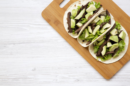 Tortillas with grilled beef and avocado on the bamboo board on a white wooden table. Top view, from above, overhead. Copy space.