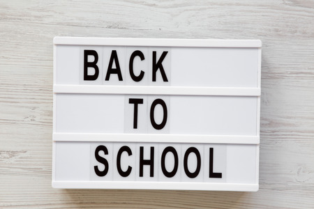 Back to school word on lightbox over white wooden surface, from above. Top view, overhead.