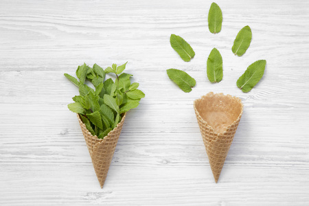 Waffle sweet ice cream cones with mint on white wooden background, top view. Flat lay, overhead, from above.