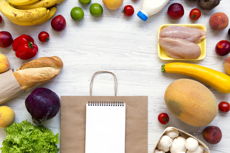Shopping concept. Set of various groceries with paper bag and notepad on white wooden table. Cooking food background. Flat lay of fresh foods. Top view, overhead, from above. Space for text.